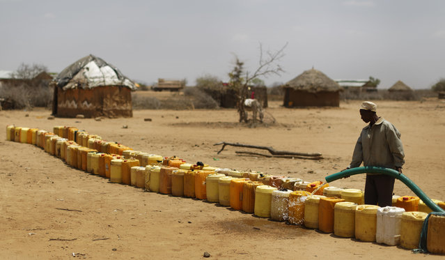 A man fills a long line of plastic water containers from a tanker, in the drought-affected village of Bandarero, near Moyale town on the Ethiopian border, in northern Kenya, Friday, March 3, 2017. (Photo by Ben Curtis/AP Photo)