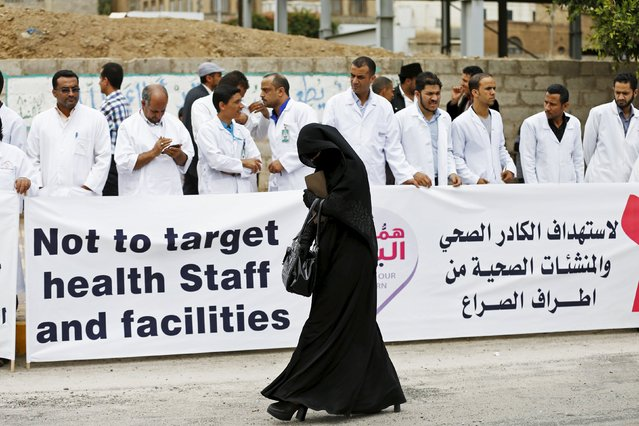 A woman walks past Health workers demonstrating against a blockade on Yemen imposed by a Saudi-led coalition, outside the headquarters of the United Nations in Yemen's capital Sanaa May 7, 2015. (Photo by Khaled Abdullah/Reuters)