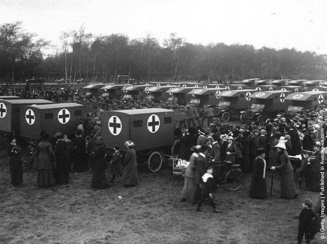 1914: Civilians watch as troops practice amongst a convoy of ambulances at Pilthey