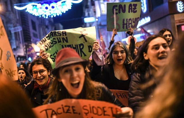 People chanr slogans as they march down Istiklal Avenue during a feminist night march to mark International Women's Day in Istanbul on March 8, 2017. (Photo by Bulent Kilic/AFP Photo)