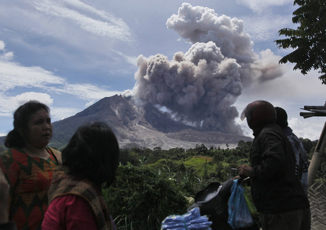 Villagers watch as Mount Sinabung releases pyroclastic flows in Tiga Pancur, North Sumatra, Indonesia, Saturday, June 13, 2015. The volcano, which was put on it highest alert level last week, has sporadically erupted since 2010 after being dormant for 400 years. (AP Photo/Binsar Bakkara)