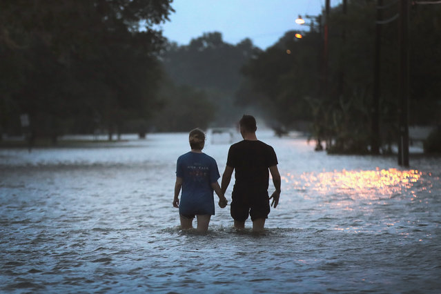 A couple strolls down Lakeshore Drive along the shore of Lake Pontchartrain after it was flooded in the wake of Hurricane Barry on July 13, 2019 in Mandeville, Louisiana. The storm, which made landfall this morning as a category one hurricane near Morgan City, caused far less damage and flooding than had been predicted. Flash flood watches were issued throughout much of Louisiana and as far east as the Florida panhandle as the storm was expected to dump more than a foot of rain in many areas and up to 25 inches in some isolated locations. Many areas are now expected to get less than half of the original projections. (Photo by Scott Olson/Getty Images)