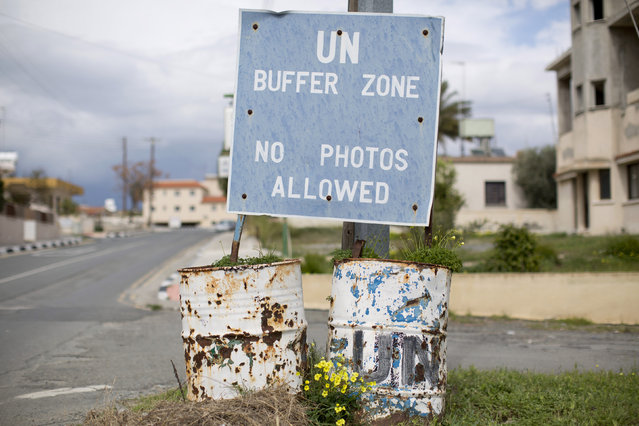 A sign marking the boundary of the United Nations buffer zone stands in the village of Pyla in Cyprus March 11, 2014. Pyla is one of a few villages in the UN buffer zone, and it is home to a mixed community of both Greek and Turkish Cypriots. (Photo by Neil Hall/Reuters)