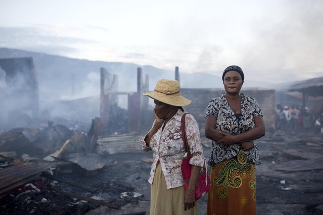 Women stand in the smoldering remains after a fire at a market in Port-au-Prince, Haiti, Monday March 20, 2017. A fire has engulfed much of a popular marketplace in Haiti's capital where hundreds of impoverished vendors sell their wares. The flames have destroyed numerous wooden stalls and a warehouse storing inventory including fabrics and used clothes. There are no reports of deaths or injuries. Despondent vendors at Port-au-Prince's sprawling Croix de Boussales market are picking through the ashes Monday looking for anything to salvage. The blaze started sweeping through the market late Sunday. The cause isn't immediately known. (Photo by Dieu Nalio Chery/AP Photo)