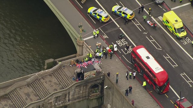 """In this image taken from video  emergency personnel gather around a body on the southside of Westminster Bridge that leads to the  Houses of Parliament in London, Wednesday, March 22, 2017 after the House of Commons sitting was suspended as witnesses reported sounds like gunfire outside. The leader of Britain's House of Commons says a man has been shot by police at Parliament. David Liddington also said there were """"reports of further violent incidents in the vicinity"""". (Photo by ITN via AP Photo)"""