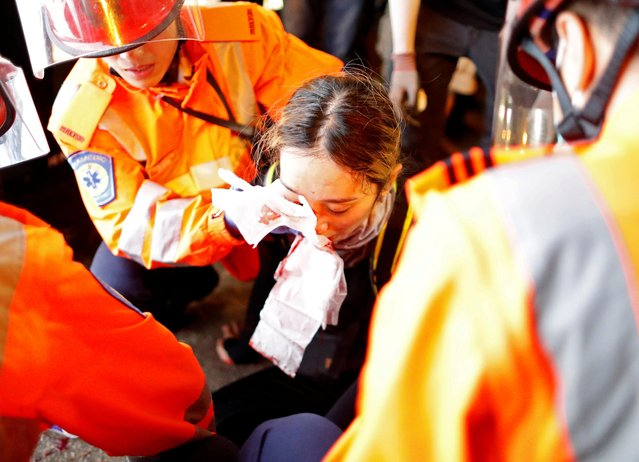 An injured young female medic receives medical assistance after being hit by a pellet round in the right eye during a demonstration in Tsim Sha Tsui neighbourhood in Hong Kong, China, August 11, 2019. (Photo by Issei Kato/Reuters)