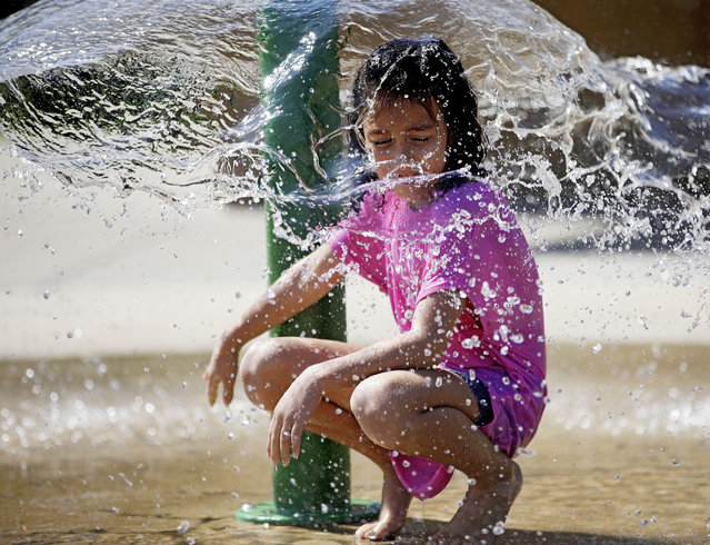 Abigail Sisney, 8, cools down from the hot weather in the splash pad at Rayola Park in Owasso, Okla., Monday, August 12, 2019. (Photo by Mike Simons/Tulsa World/Tulsa World via AP Photo)