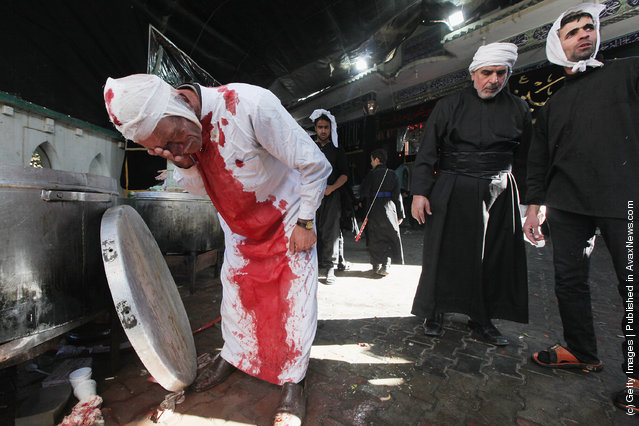 A Shi'ite worshiper washes himself after cutting his scalp in a ritual display of mourning during an Ashura commemoration ceremony outside Kadhimiya shrine in Baghdad, Iraq