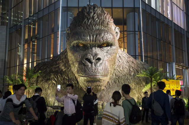 """Citizens look at a giant King Kong statue at TaiKoo Hui on March 30, 2017 in Guangzhou, Guangdong Province of China. The five-metre-tall King Kong statue, which resembles its prototype in the film """"Kong: Skull Island"""", was built to promote the film """"Kong: Skull Island"""" on the square of TaiKoo Hui. (Photo by VCG/VCG via Getty Images)"""