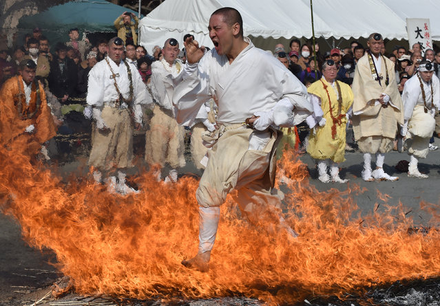 """A Buddhist devotee dashes barefoot through flames during the Nagatoro Hi-Matsuri, or fire-walking festival, to herald the coming of spring at the Fudoji temple in Nagatoro town, Saitama prefecture on March 5, 2017. Hundreds of people following Buddhist ascetics participated in the fire-walking festival to """"purify the mind and body"""" and to pray for good health and safety. (Photo by Kazuhiro Nogi/AFP Photo)"""