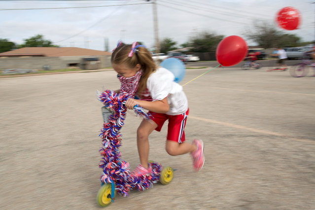 Jessie Parker, 7, rides her decorated scooter for the Odessa Christian School camps 4th of July patriotic parade on Thursday, July 2, 2015, in Odessa, Texas.  (Photo by Courtney Sacco/Odessa American via AP Photo)