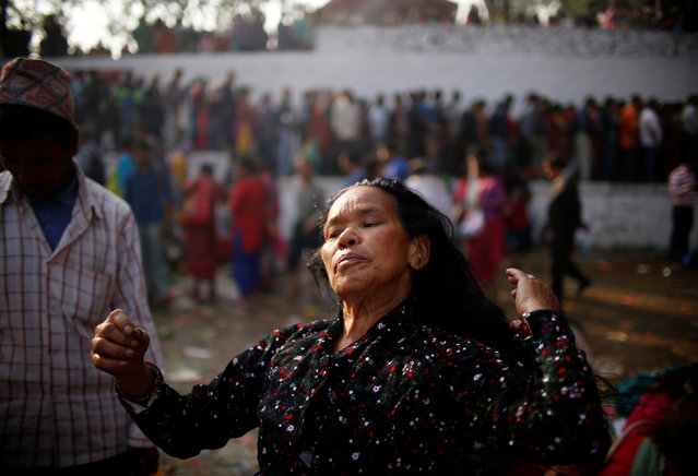 A devotee adjusts her hair after taking a holy bath at Matathirtha to commemorate her departed mother during Mother's Day in Kathmandu, Nepal, May 6, 2016. (Photo by Navesh Chitrakar/Reuters)