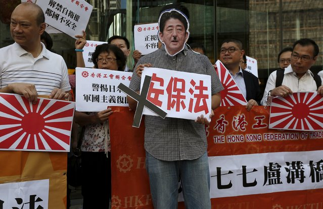 "A protester wears a cutout of a defaced portrait of Japanese Prime Minister Shinzo Abe while holding a sign which reads ""security bill"", as others carry illustrations of the Japanese military flag, during a demonstration outside the Japanese consulate in Hong Kong, China July 7, 2015. Tuesday marks the 78th anniversary of the start of the Sino-Japanese war. (Photo by Bobby Yip/Reuters)"