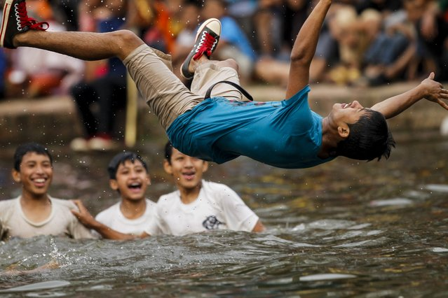 """A Nepalese youth jumps on the Gahana Pokhari -A Jwel Pond before participating in a Gahana Khojne festival in Kathmandu, Nepal, 16 April 2014. Hundreds of local youths carry chariot of Goddess """"Tudaldev"""" to search goddess lost Jwellery during a traditional 'Gahana Khojne Jatra' which means """"searching for jewels"""" at the pond. (Photo by Narendra Shrestha/EPA)"""