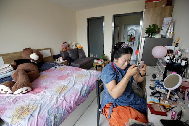 """Li Doudou applies makeup before attending a performance of the """"guqin"""" traditional musical instrument, an ancient seven-stringed zither, at her rental home in Hebei province, China, August 18, 2019. """"The biggest change for me personally is it gives me more self-confidence"""", she said. """"When I wear Hanfu, I feel like I'm the most beautiful person in the world"""". (Photo by Jason Lee/Reuters)"""