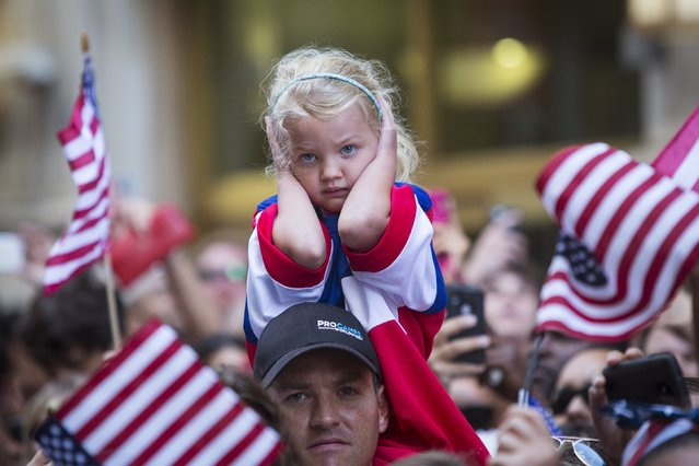 A fan of the U.S. women's soccer team blocks her ears during the ticker tape parade to celebrate their World Cup final win over Japan on Sunday, in New York, July 10, 2015. (Photo by Andrew Kelly/Reuters)