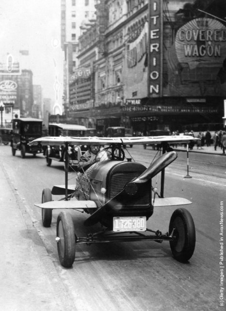 A car with wings and a propeller protruding from the radiator grille drives through Times Square, New York. The invention of A.H. Russell of Nutley, New Jersey, 1924