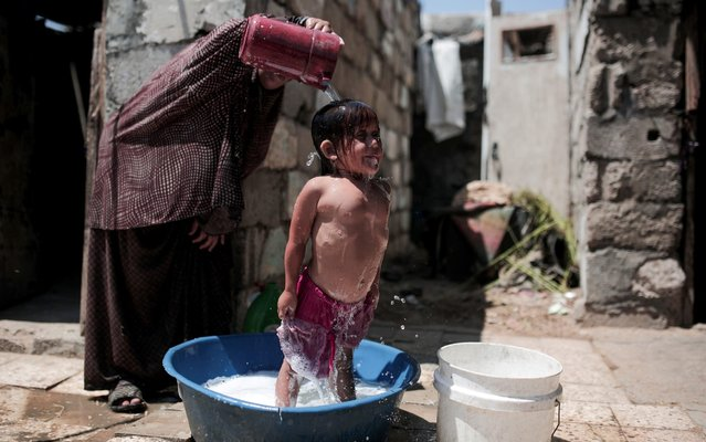 A woman washes a kid in a plastic basin on a hot day at in Gaza City, Gaza on August 24, 2019. (Photo by Mustafa Hassona/Anadolu Agency via Getty Images)