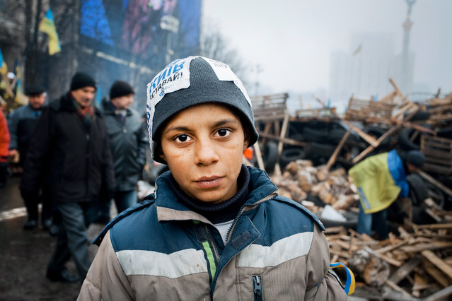 """Gavroche"". The serious boy helps people to build barricades in Kiev. He came with friends from a neighboring town. Thousands of people had four months of anti-mafia rally on Euromaidan, on the main square of the ukrainian capital. On the boy's hat pasted stickers ""Kiev, wake up!"". Photo location: Kiev, Ukraine. (Photo and caption by Vadym Kulykov/National Geographic Photo Contest)"