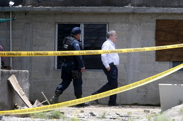 """National Security Commissioner Monte Alejandro Rubido (R) inspects a warehouse where a tunnel connected to the Altiplano Federal Penitentiary and used by drug lord Joaquin """"El Chapo"""" Guzman to escape was located in Almoloya de Juarez, on the outskirts of Mexico City, July 15, 2015. (Photo by Edgard Garrido/Reuters)"""