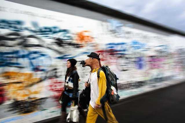 """A street musician who calls  himself, """"The Neigh Kid Horse"""", walks in front of the remains of the Berlin Wall Germany, on May 12, 2014. (Photo by Markus Schreiber/Associated Press)"""