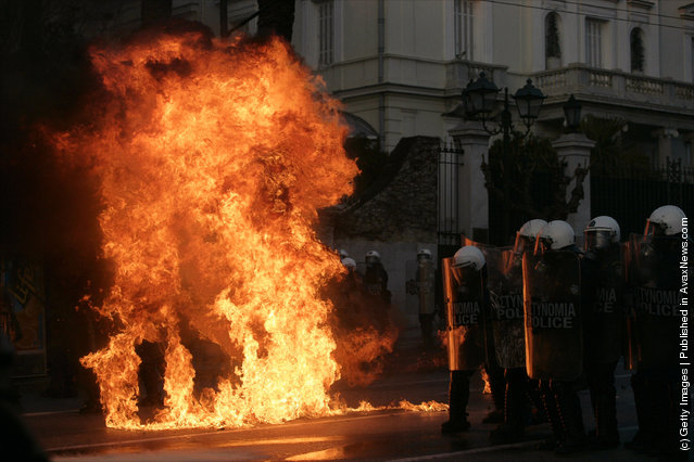 Police clash with protestors in the street as it burns during a demonstration against the new austerity measures on February 12, 2012 in Athens, Greece