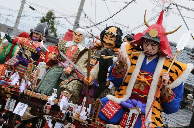Festival goers carry huge paper dolls of historical Japanese figures on the carts during the Mikuini annual festival on May 20, 2014 in Sakai, Japan. The annual festival takes place from May 19-21 and is attended by thousands of visitors. During the festival people dressed in traditional Japanese costumes pull carts carrying 6 meter high dolls of Japanese historical figures through the narrow streets. The origins of the festival are unclear but its history can be traced back more than 250 years. (Photo by Buddhika Weerasinghe/Getty Images)