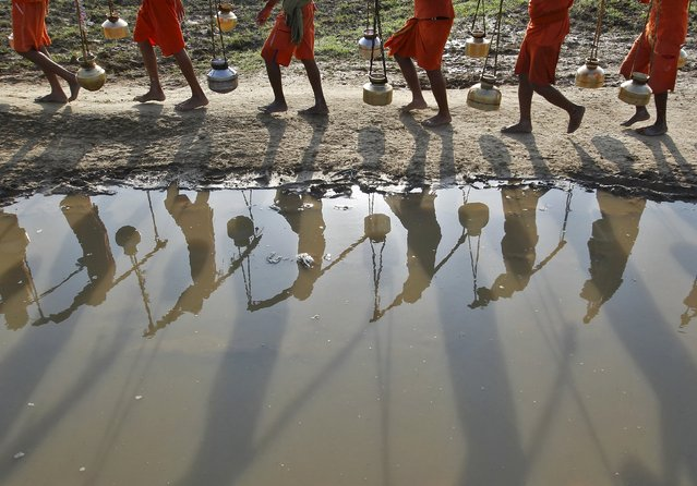Kanwarias or devotees of Hindu god Shiva carrying pitchers are reflected in a puddle as they walk after filling the pitchers with the water from the river Ganges in Allahabad, India, July 13, 2015. Hundreds of Kanwarias carried holy water from Ganga to Padilla Mahadev temple to worship god Shiva. (Photo by Jitendra Prakash/Reuters)