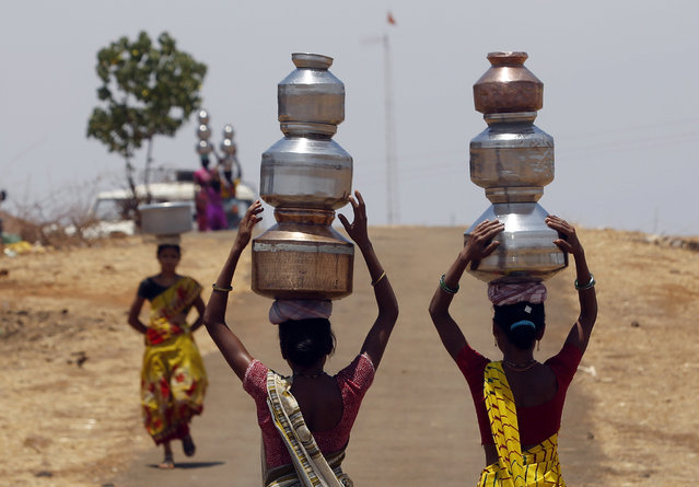 Indian women walk home after collecting drinking water from a well at Mengal Pada in Thane district in Maharashtra state, India, Wednesday, May 4, 2016. Much of India is reeling under a weekslong heat wave and severe drought conditions that have decimated crops, killed livestock and left at least 330 million Indians without enough water for their daily needs. (Photo by Rajanish Kakade/AP Photo)