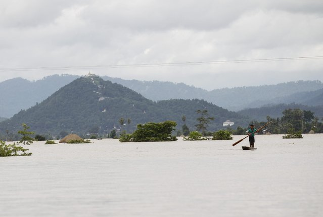 A man rows his boat along a flooded rice field in Kawlin township, Sagaing division, Myanmar, July 21, 2015. (Photo by Soe Zeya Tun/Reuters)