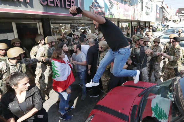 Anti-government protesters scuffle with Lebanese army soldiers in the town of Zouk Mosbeh, north of Beirut, Lebanon, Tuesday, November 5, 2019. Lebanese troops deployed in different parts of the country Tuesday reopening roads and main thoroughfares closed by anti-government protesters facing resistance in some areas that led to scuffles. (Photo by Hassan Ammar/AP Photo)