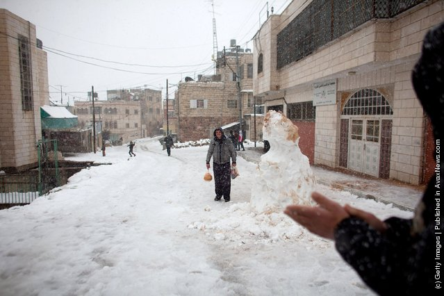 People walk on a snow covered street on March 2, 2012 in Hebron, West Bank