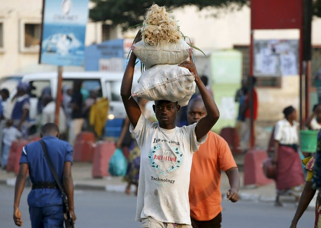 A man carries bags of vegetables at marketplace in Burundi's capital Bujumbura, as the country awaits the results of Tuesday's presidential elections, July 23, 2015. Opposition politicians have accused President Pierre Nkurunziza of violating the constitution by running for a third term and boycotted the election in the world's third poorest country. (Photo by Mike Hutchings/Reuters)