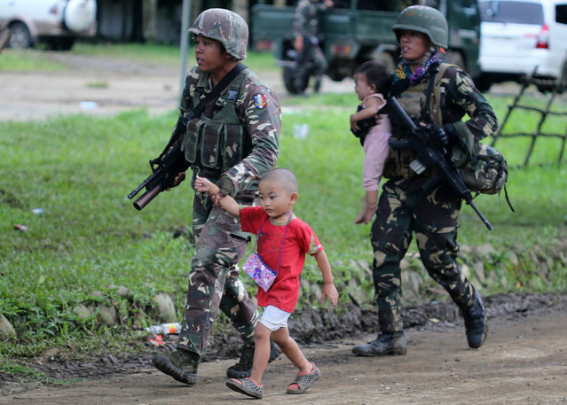 Filipino soldiers hold on to fleeing children following reports of fresh clashes between government troops and rebels in Marawi City, Mindanao Island, southern Philippines, 25 May 2017. According to media reports, President Rodrigo Duterte declared martial law on the southern island of Mindanao in response to a new armed offensive by the Maute group, one of the jihadist bands operating in the region. On May 23, militants from the Maute group – an organization linked to the so-called Islamic State (or IS or ISIS) – had captured Marawi, a city with a population of 200,000 people, and laid siege on a hospital for hours, and set a church, a college and the city's prison to fire, while holding over 10 people hostage. The Maute group is an Islamic armed organization based in Lanao del Sur that first emerged in 2012 under the name of Khilafah Islamiyah Movement (KIM), but adopted the name EI-Ranao two years later to indicate its affiliation with the so-called Islamic State. (Photo by Linus G. Escandor Ii/EPA)