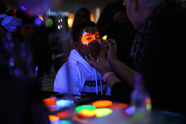 A boy has his face painted with fluorescent paint during the Vivid Sydney festival of light and sound in Sydney, Australia, May 26, 2017. (Photo by Steven Saphore/Reuters)
