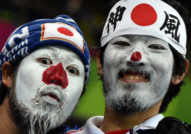Japanese fans with their faces painted in the colours of their national flag await the kick-off of a Group C football match between Ivory Coast and Japan at the Pernambuco Arena in Recife during the 2014 FIFA World Cup on June 14, 2014. (Photo by Javier Soriano/AFP Photo)