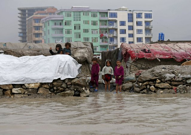 Internally displaced Afghan children stand outside their makeshift houses as water cover their path during a rainy day in Kabul, Afghanistan May 11, 2015. (Photo by Mohammad Ismail/Reuters)