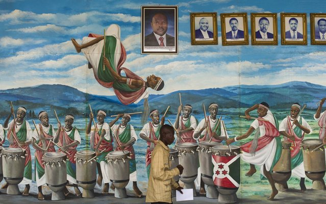 A man walks past a painted mural with drummers and dancers and portraits of Burundi's presidents past and present, in the National Assembly in Bujumbura, ahead of the opening session of the National Assembly in Bujumbura, on July 27, 2015. Burundi, where President Pierre Nkurunziza won an expected third term on July 24, has since late April been rocked by deadly protests against his divisive bid for re-election. (Photo by Phil Moore/AFP Photo)