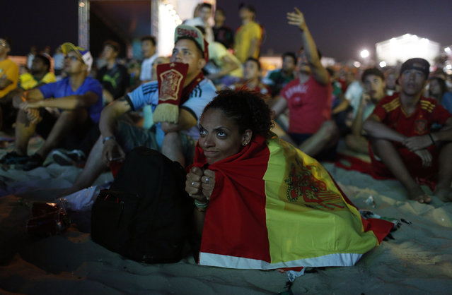 A Spanish soccer fan reacts as she watches the 2014 World Cup soccer match between the Netherlands and Spain on a large screen at Copacabana beach in Rio de Janeiro, June 13, 2014. (Photo by Pilar Olivares/Reuters)