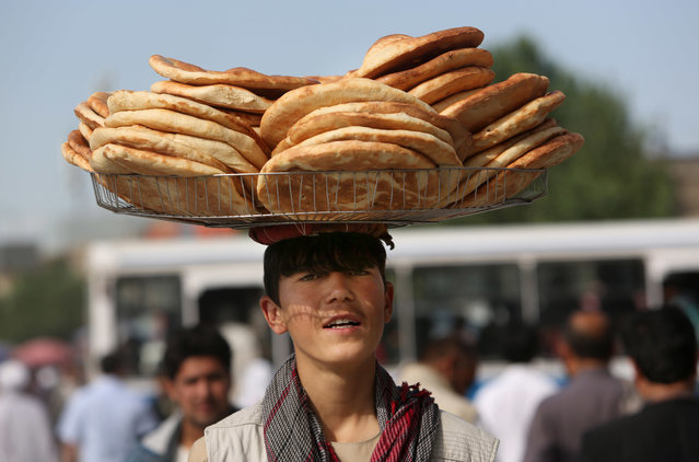 An Afghan street vendor carries bread on his head ahead of the upcoming holy fasting month of Ramadan in Kabul, Afghanistan, Sunday, June 5, 2016. (Photo by Rahmat Gul/AP Photo)