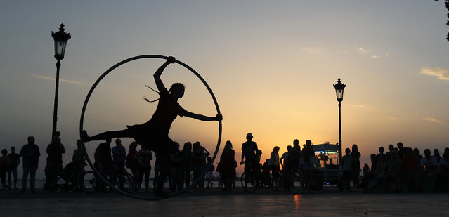 An Argentinian street performer is watched by spectators, in front of city's landmark, the White Tower,  at sunset, on the seaside promenade in the northern Greek city of Thessaloniki, Tuesday, June 24, 2014. (Photo by Nikolas Giakoumidis/AP Photo)