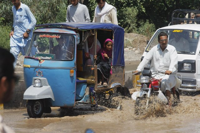 Vehicle drivers and a motorcyclist wade through a flooded street following recent heavy rains in Peshawar, Pakistan, Monday, July 27, 2015. Heavy monsoon rains lashed an already-deluged northern Pakistan, killing tens of people so far in different parts of the country. (Photo by Muhammad Sajjad/AP Photo)
