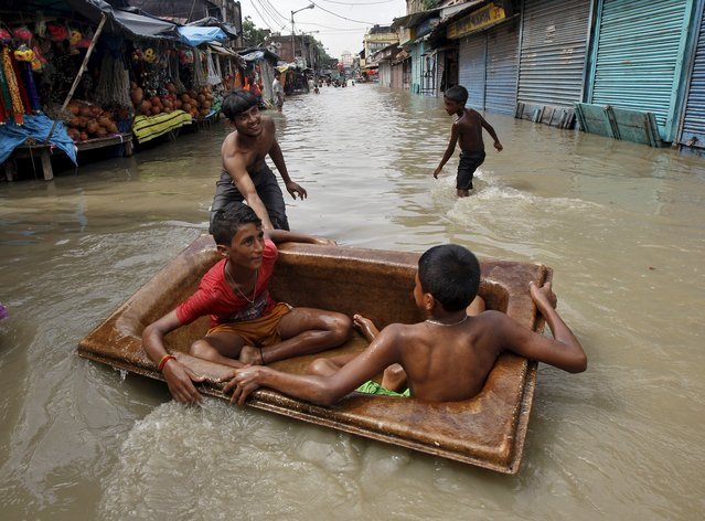 Boys play on a floating tub in a flooded road after heavy monsoon rains in the eastern India caused the rise in water levels of river Ganga and its tributaries in Kolkata, India, August 3, 2015. (Photo by Rupak De Chowdhuri/Reuters)