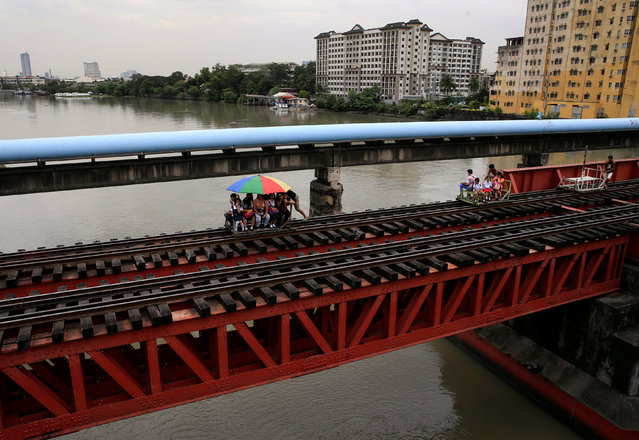 Commuters ride a makeshift trolley over a railroad bridge as a cheaper and faster alternative mode of transportation in metro Manila, Philippines January 25, 2017. (Photo by Romeo Ranoco/Reuters)