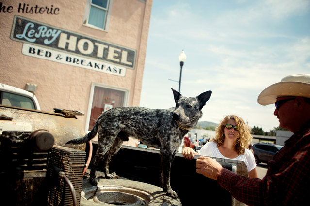 Dog Silver, Deb Kenobbie, of Iowa, and Roger Kenobbie, of Kimball, South Dakota, watch bike traffic along Main Street in downtown Custer, South Dakota as bikers participate in the annual Sturgis Motorcycle Rally on August 3, 2015. (Photo by Kristina Barker/Reuters)