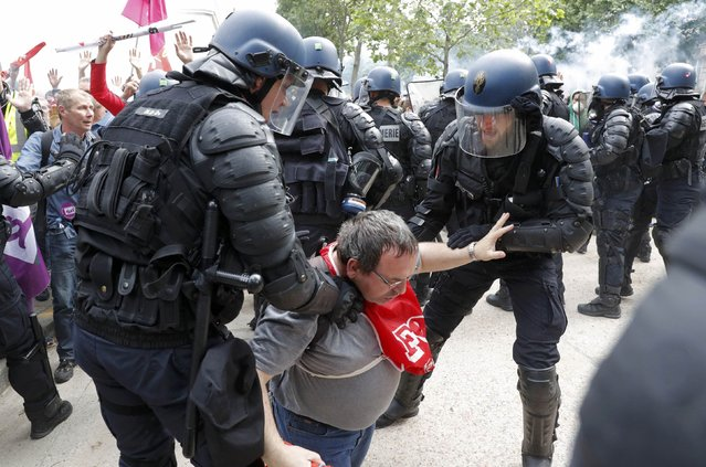 French gendarmes help a French FO labour union employee during a demonstration in Paris as part of nationwide protests against plans to reform French labour laws, France, June 14, 2016. (Photo by Philippe Wojazer/Reuters)
