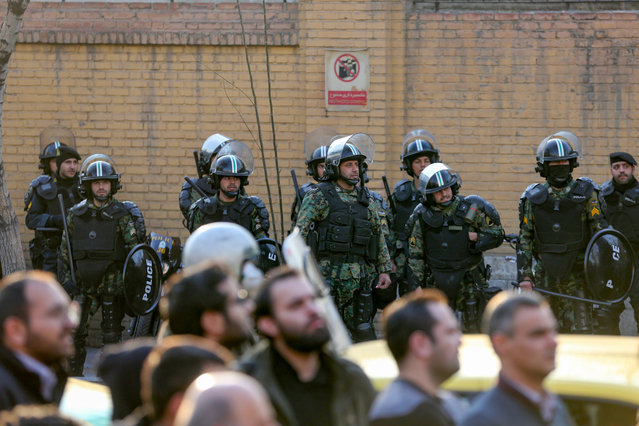 """Iranian security forces stand guard in front of the British embassy in the capital Tehran on January 12, 2020 following the British ambassador's arrest for allegedly attending an illegal demonstration. Chanting """"Death to Britain"""", up to 200 protesters rallied outside the mission a day after the brief arrest of British ambassador Rob Macaire at a memorial for those killed when a Ukraine airliner was shot down. (Photo by Atta Kenare/AFP Photo)"""