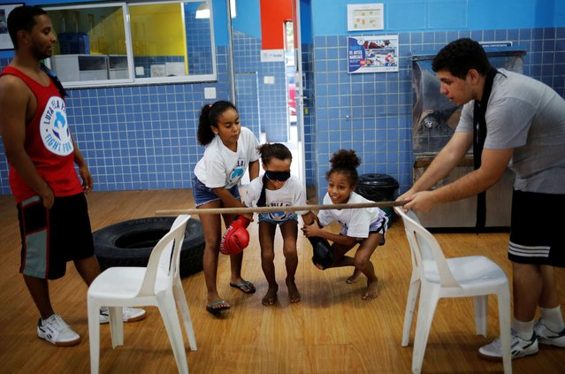 Children practice next to teachers during an exercise session at a boxing school, in the Mare favela of Rio de Janeiro. (Photo by Nacho Doce/Reuters)