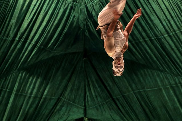 """An acrobat does a flip mid-air during a media preview of Cirque Du Soleil's Kooza Tuesday, July 11, 2017, in Singapore. Kooza is a return to the origins of Cirque du Soleil, combining two circus traditions of acrobatic performance and the art of clowning. The name Kooza is inspired by the Sanskrit word """"koza"""" which means """"box"""", or """"treasure"""", and was chosen because of the underlying concept of the production, which is the idea of a """"circus in a box"""". (Photo by Wong Maye-E/AP Photo)"""