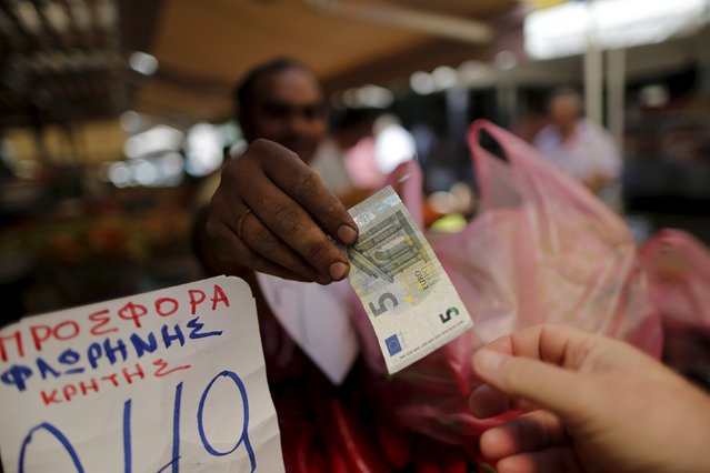 A vendor gives a five Euro bank note back to a customer at the central market in Athens, Greece, July 8, 2015. (Photo by Christian Hartmann/Reuters)